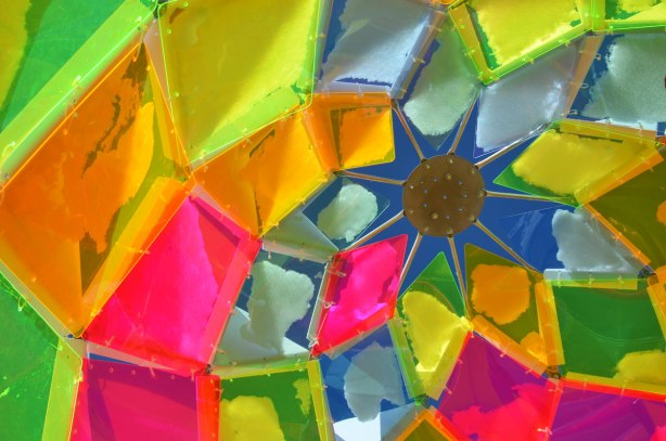 Looking from inside a dome shaped structure that is made of geometric shapes of coloured plastic, looking to the bright blue sky, with snow on some of the pieces of plastic.  Lots of bright colours.