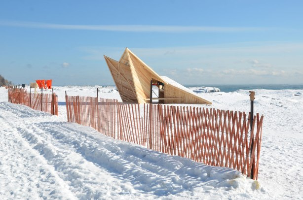 Beach in winter, snow, snow fence and lots of blue sky.  There is a wooden art installation that is also seating for those who want to sit and look out over the cold lake.