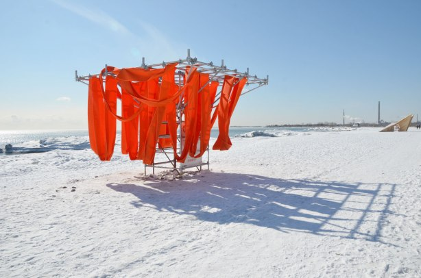 The art installation, Sling Swing, in the breeze on a frozen snow covered beach.  It consists of large pieces of orange fabric slings hanging from a metal frame. One can use the slings as swings.