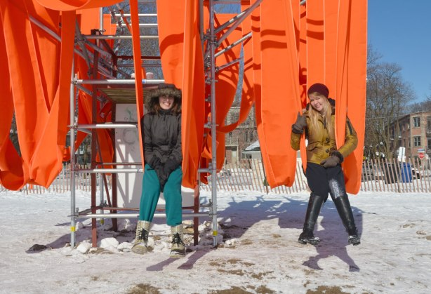 Two women sitting on the orange sling swings on a cold winter day at the beach