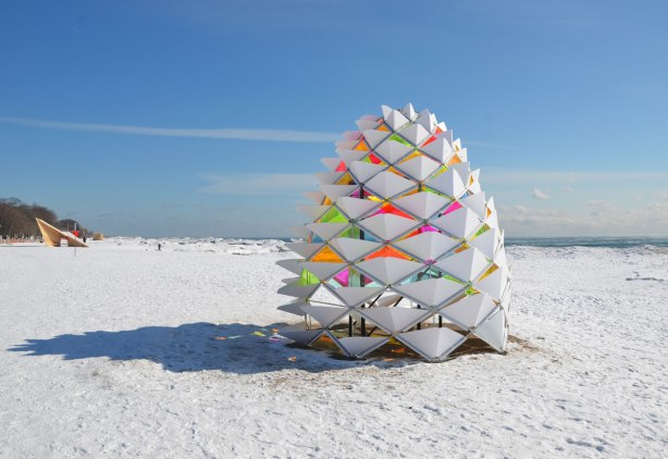 Art installation that looks like a giant white pinecone on the beach in winter.  The inside of the parts of the cone are bright translucent coloured plexiglass