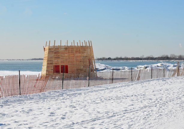 Wooden structure on a winter beach between a snow fence and the lake