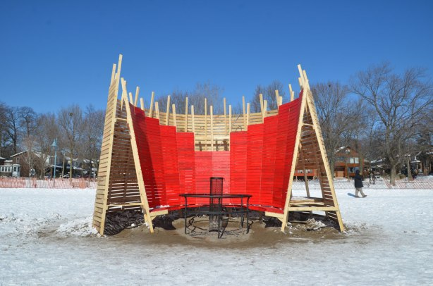 wooden structure on the beach in winter.   Part in painted red.  It is supposed to be a large chair, semi-circle, can seat a number of people.