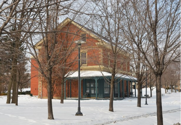 old Dempsey store, restored and now in a park setting.  Two storey brick house with some yellow brick trim, porch that wraps around the front of the building.  Surrounded by trees, winter time so no leaves and there is snow on the ground.