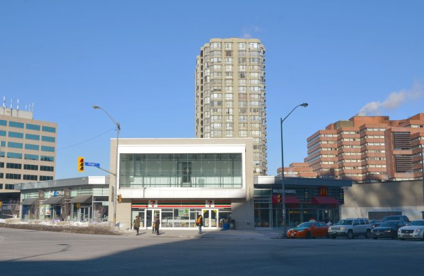 Northwest corner of Yonge and Sheppard in March of 2015, low rise building angled across the corner with McDonalds and 7 11 stores.  Tall apartment building behind.  The intersection is of two 6 lane roads so it is big and wide.