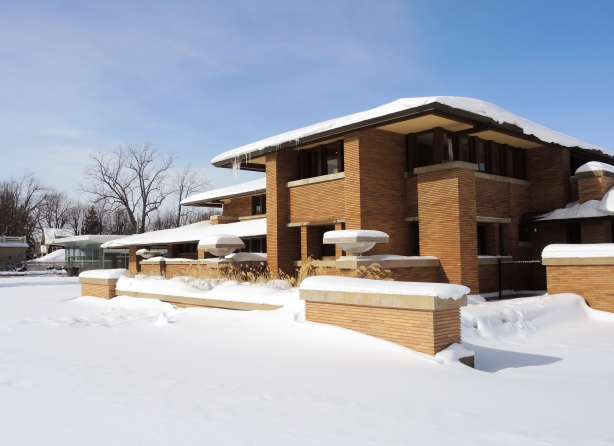 Exterior of the Darwin Martin House in winter. A low rise house designed by Frank Lloyd Wright in his prairie style. Lots of snow and blue sky.