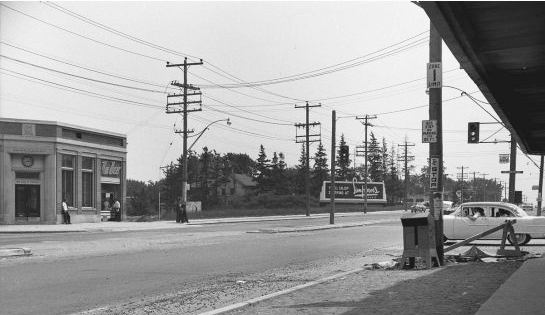 An old black and white photo from 1955 showing the intersection of Yonge and Sheppard.  Not much development, an old car is waiting at a street light.