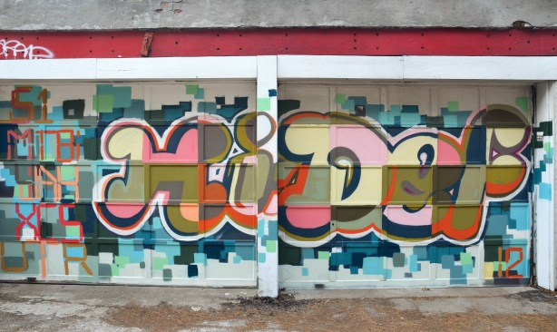 "Graffiti painting on a garage door of the words ""Hi Def"" in rounded fat letters with colours in pinks greens and black squares."