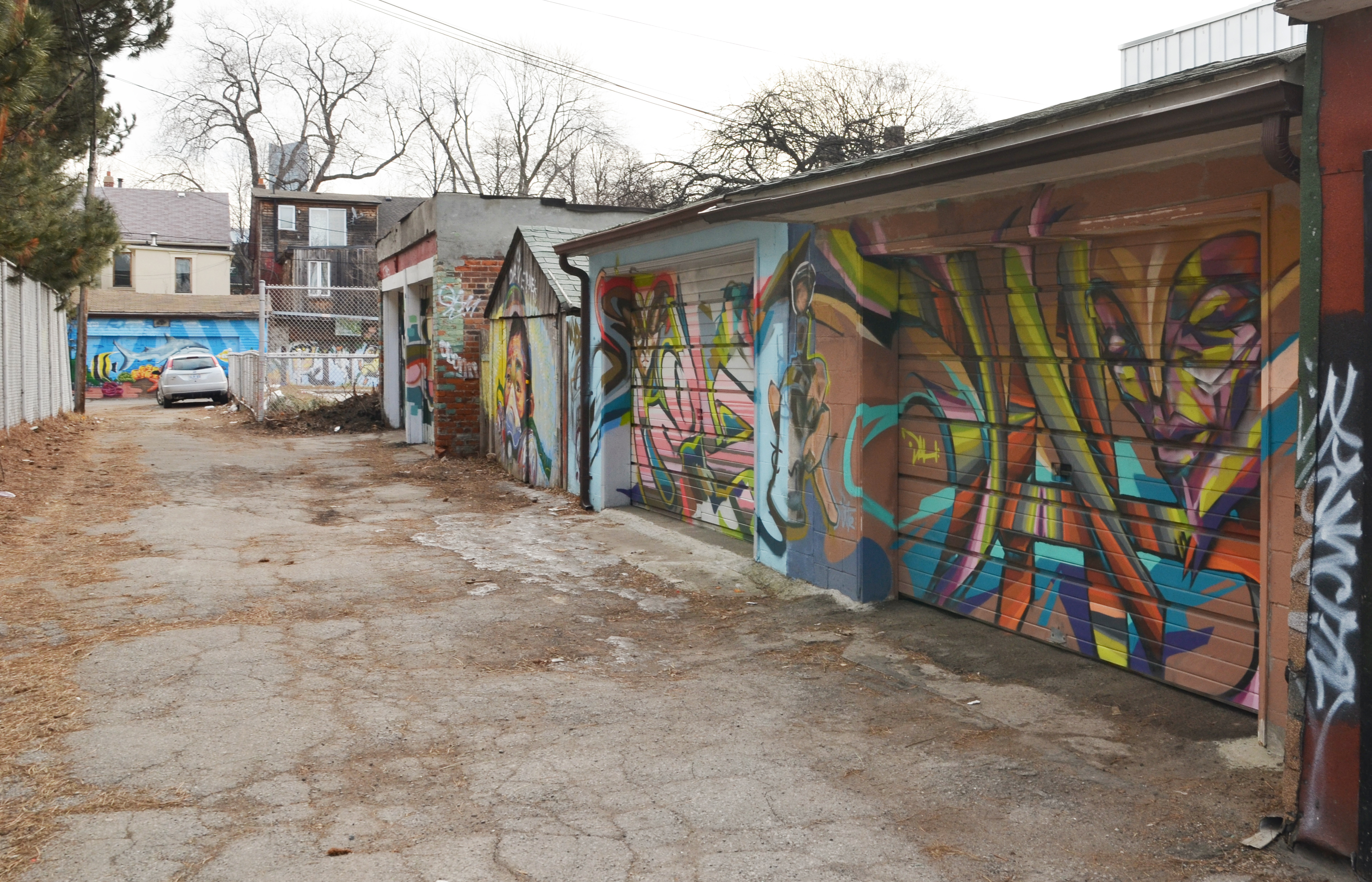 Longer View Of Part Of An Alley Showing The Street Art Covered Garage Doors.