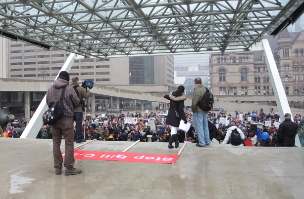 View of a protest from the back of a stage. The backs of 4 photographers is to the camera. They are taking pics of the crowd.