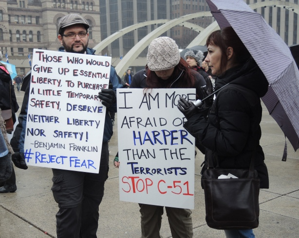 A group of 3 people.  A woman on the right is holding a purplish grey umbrella.  The other 2 people are holding protest signs.