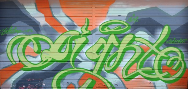 "Graffiti tag on a garage door in an alley, green tag on blue and orange background.  The tag, or word, says ""sighto"" or something like that."
