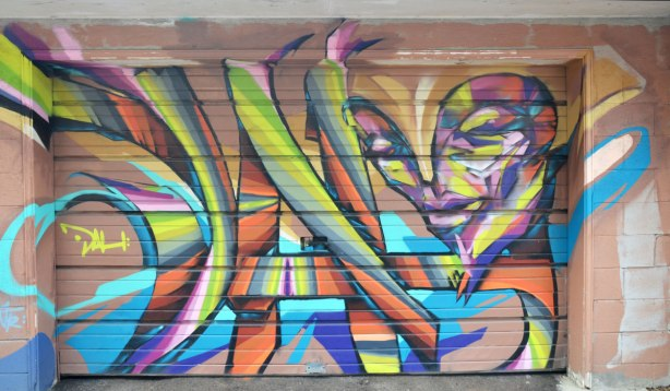 Graffiti on a garage door.  A face is in the top right corner and she is looking down towards the ground.  Stylized.