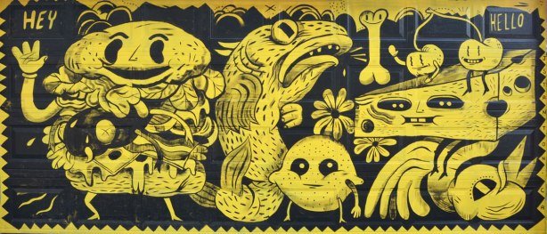 A mural on a garage door, all yellow and black, stylized figures a fish, a bone, a wedge of cheese with a face, two cherries made into little figures with eyes, mouth and legs, a large sandwich with a face on the bun as well as arms and legs, also a lemon with eyes, arms and legs.  personified food,,