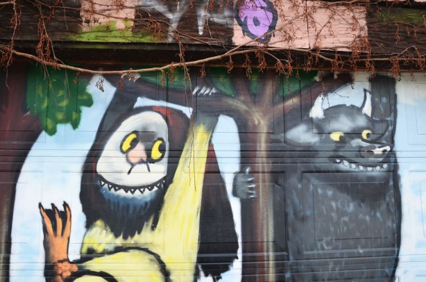 "Close up of a Mural on a garage door of Max and the Wild Things, characters from the children's book ""Where the Wild Things Are"" .  Two of the wild things are  are swinging from tree branches."