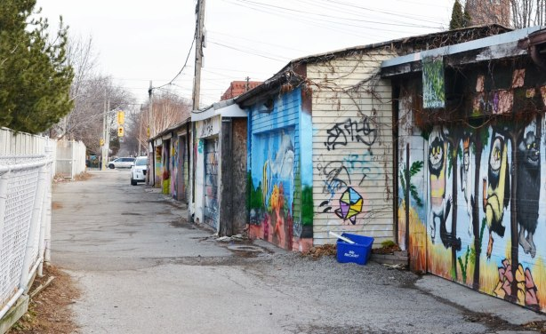 north end of an alley with garage doors on the right, white chain link fence on the left.   The garage doors are covered with street art and graffiti.