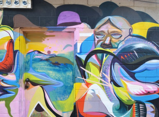 colourful graffiti painting of a man's face surrounded by a lot of abstract shapes