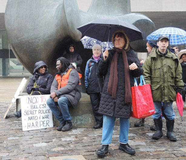 """A group of people around Henry Moore's sculpture """"the Archer"""" in Nathan Phillips Square.  They are there for the anti Bill C51 protest.  A couple are sitting and talking to each other.  Others are standing under umbrellas."""