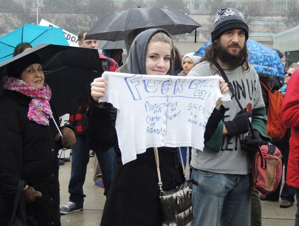 "A young woman is holding a piece of white fabric on which words have been printed:  ""Fuck bill C-51"" is in larger letters."