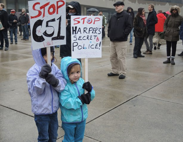"Two  young girls are holding protest signs.  One says ""Stop Harpers Secret Police"" and the other says ""Stop C51""."