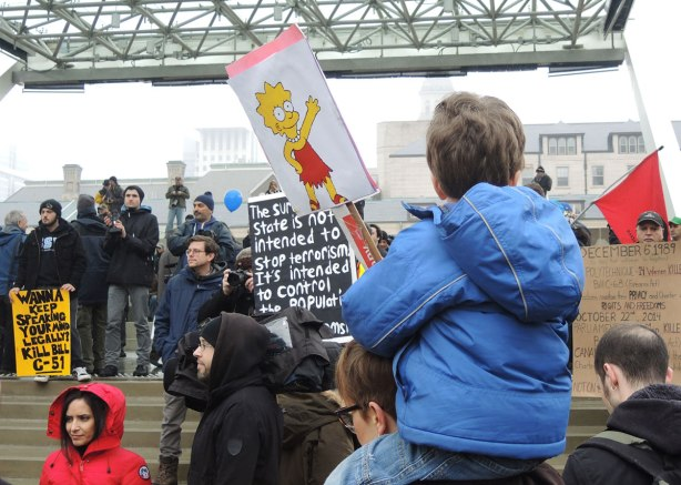 A boy on his mother's shoulders is holding a sign with a picture of Lisa on it.