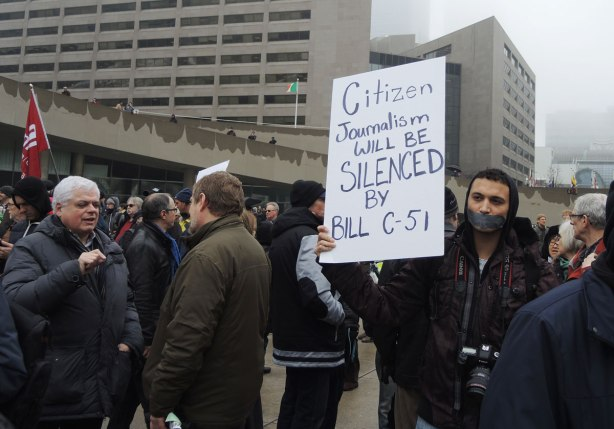 "People at a protest rally.  One man has duct tape over his mouth and he is holding a placard that says ""Citizen journalism will be silenced by Bill C-51"""