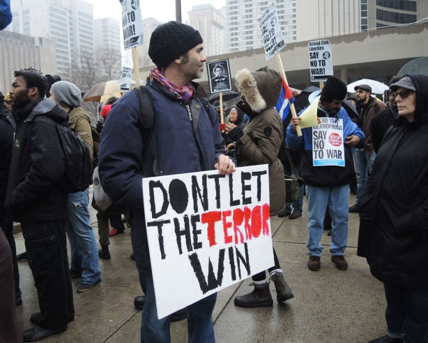 A man is holding a placard that says Don't Let the Terror Win at a protest