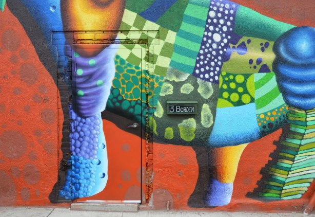 birdo street art, close up of multicoloured creature over a doorway.  Belly and legs are visible in the photo