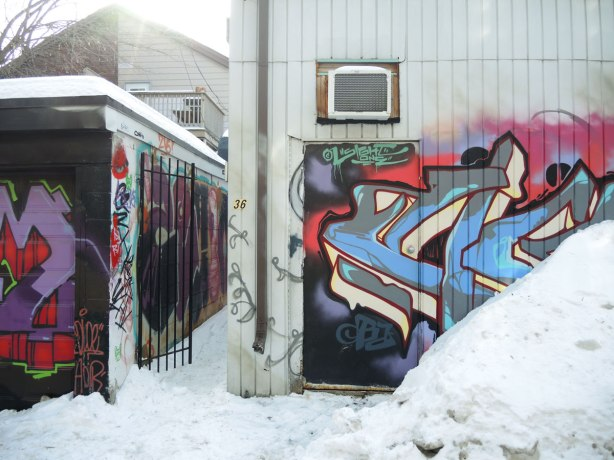 Graffiti on a garage door obscured by a large pile of snow.  Open metal gate between two garages, graffiti can be just seen down the wall on one of the garages, beyond the gate.