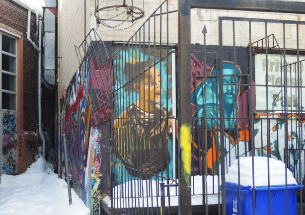Two graffiti faces on a wall, one woman and one man. Metal bars surrounding a small parking spot behind the building partially obscure the wall.