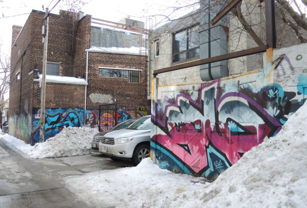 backs of buildings, cars parked behind the buildings, piles of snow on the side of the alley, graffiti on the walls and garage doors.