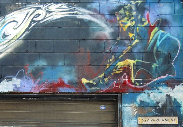 graffiti painting of a musician, trumpet player in yellow on blue background, above a garage door in a lane