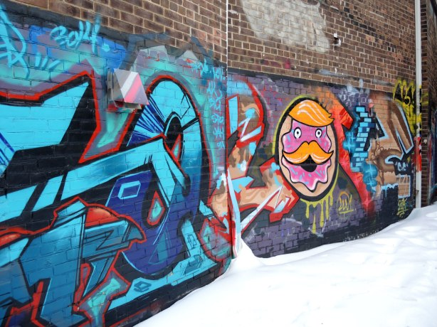 Graffiti street art, smiley man's face in pink with orange hair and orange moustache.  Also abtracts in blues.