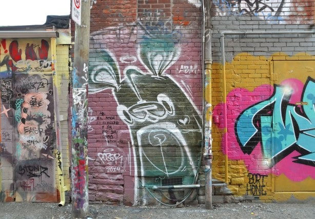 large greenish brown poser bunny in Graffiti Alley on pinkish purple background.   Bight yellow, pink and blue tag to the right and a door covered with small tags to the left
