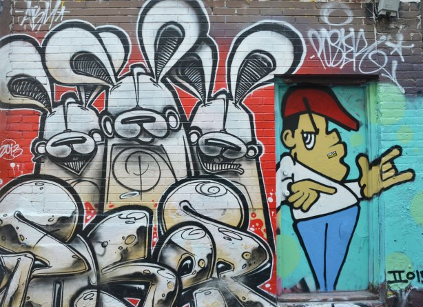 three black and white poser bunnies on red background with black and white tag in front  in Graffiti Alley.  They are beside a doorway on which a man has been painted - red hair, white T-shirt and blue pants.  Stylized, shrugging his shoulders and holdin his hands at waist level.