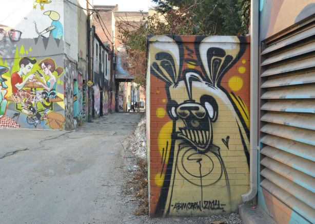 light brown poser bunny in Graffiti Alley - about 30 cm wide and 75 cm high on a wall that is perpendicular to the alley, Graffiti Alley is in the background.  Signed ambcrew 2014