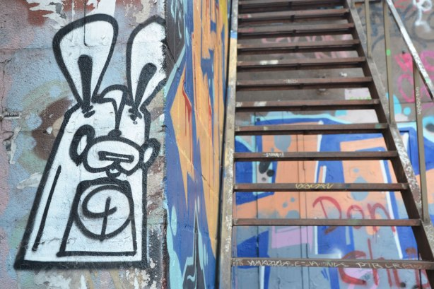 small black and white poser bunny in Graffiti Alley on a wall beside a metal exterior staircase