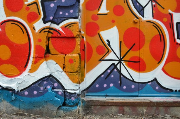 close up of a door and doorstep that is incorporated into new graffiti tag art in the alley, red with yellow polka dots on blue background
