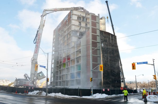 Two very large cranes are being used to demolish a large apartment building on the corner of Dundas and Sumach streets.  Some men in bright yellow vests are directing traffic as some of the debris is falling towards Sumach street.
