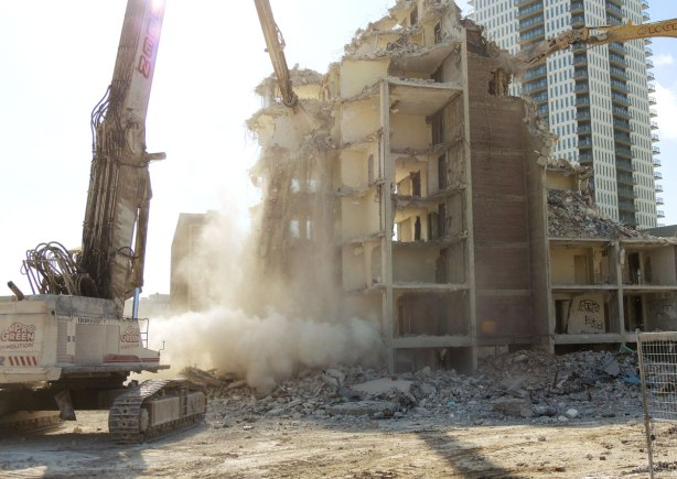 As part of the upper stories of an apartment are brought down, a cloud of dust forms as the debris hits the ground.