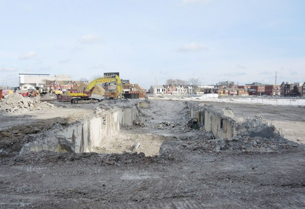A large hole in the ground where a building once stood, vacant land is around it.  A street of houses in the distance, machinery to one side.