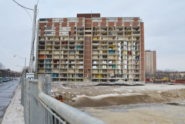 A large 14 storey brick clad apartment building in the initial stages of being demolished.