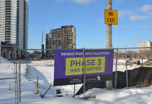 A purple and yellow sign against a metal fence that says Regent Park Revitalization Phase 3 has started.  Demolition of an apartment in the background.