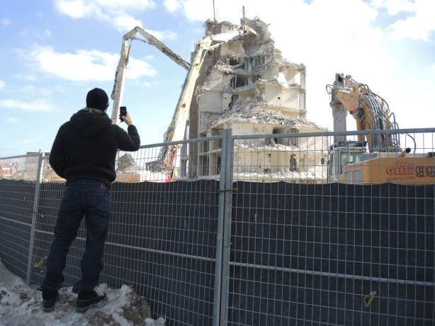 A man is taking a picture of a demolition in progress of an apartment building.