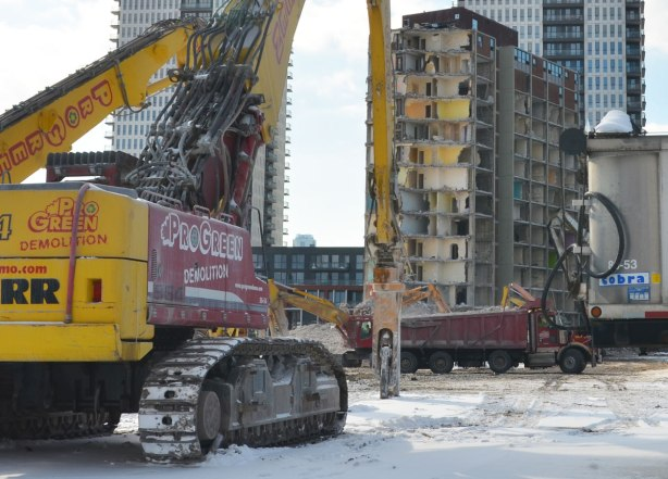 Hydraulic crane and truck and other machinery used in the demolition of the building.