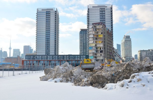Vacant lot in the forground with demolition of a building in the middle.  In the background are the new buildings that have been built in that area