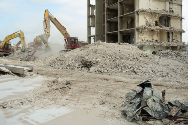 Machinery is being used to sift through the debris and rubble from a building demolition