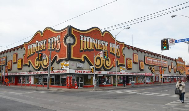"""Looking across an intersection of Bloor and Bathurst streets towards Honest Eds store with its big orange, yellow and black signs on grey cladding.  Running around the store, about the level of the top of the first storey, are signs (red lettering on white background) that read """"Only the Floors are crooked"""" , """"There's no place like this place, any place"""", """"Come in and Get Lost"""" and lastly, """"A Bargain Centre like this happens only once in a lifetime"""""""