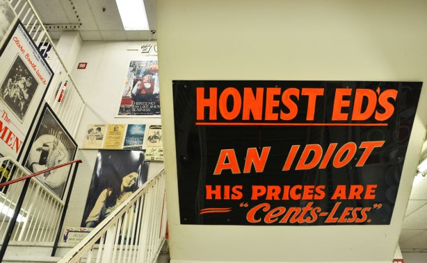 "A stairwell at Honest Eds store with a large black and red sign that reads ""Honest Ed's an Idiot, his prices are cents-less"""
