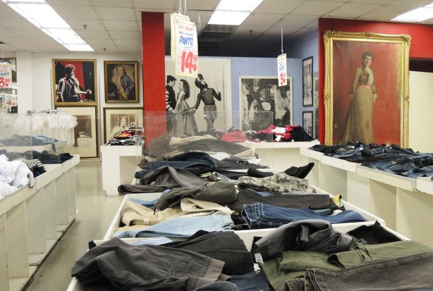 Jeans for sale, on tables in Honest Eds store.  Large black and white posters on the wall along with a colour full length portrait of a woman in a long dress.